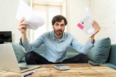 Gniewny mężczyzna płaci rachunki z laptopem i kalkulatorem jak do domu fotografia stock