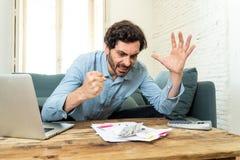 Gniewny mężczyzna płaci rachunki z laptopem i kalkulatorem jak do domu zdjęcie stock