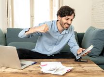 Gniewny mężczyzna płaci rachunki z laptopem i kalkulatorem jak do domu obrazy stock