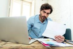 Gniewny mężczyzna płaci rachunki z laptopem i kalkulatorem jak do domu obraz royalty free