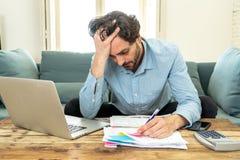 Gniewny mężczyzna płaci rachunki z laptopem i kalkulatorem jak do domu zdjęcie royalty free