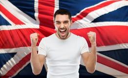 Gniewny mężczyzna pokazuje pięści nad brittish flaga obrazy stock