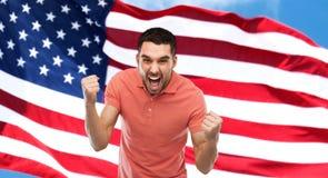 Gniewny mężczyzna pokazuje pięści nad flaga amerykańską zdjęcie stock