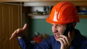 Gniewny mężczyzna pracownik budowlany krzyczy w hardhat, opowiada na telefonu smartphone obraz royalty free