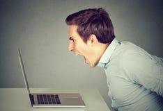 Gniewny mężczyzna pracuje na laptopie obrazy royalty free
