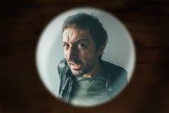 Gniewny mężczyzna przy drzwi przeglądać przez wziernej dziury Zdjęcia Royalty Free