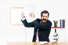 Gniewny mężczyzna roztrzaskuje laptop Zdjęcia Stock