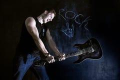 Gniewny mężczyzna trzyma gitarę i próbuje łamać je Zdjęcie Royalty Free