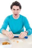Gniewny mężczyzna w błękitnym pulowerze robi papierosom z przyrządem dla ciga Zdjęcia Royalty Free
