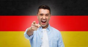 Gniewny mężczyzna wskazuje palec na tobie nad niemiec flaga Obraz Royalty Free