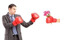 Gniewny mężczyzna z bokserskimi rękawiczkami uderzający rękę z bokserską rękawiczką obraz royalty free