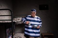 Gniewny męski więzień jest ubranym więzienia jednolitego mienia aluminiowego naczynie Obraz Royalty Free