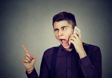 Gniewny młody człowiek krzyczy na telefonie komórkowym zdjęcia royalty free