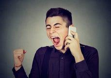 Gniewny młody człowiek krzyczy na telefonie komórkowym Fotografia Stock