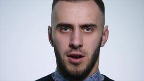 Gniewny młody człowiek na białym tle z bliska zdjęcie wideo