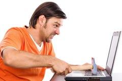 Gniewny młody człowiek przy laptopem Zdjęcia Royalty Free