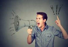 Gniewny młody człowiek trzyma krzyczeć w megafonie Fotografia Stock