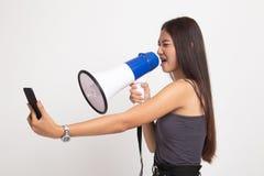 Gniewny m?ody Azjatycki kobieta krzyk z megafonem telefon kom?rkowy zdjęcia stock