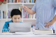 Gniewny nauczyciel karci jego ucznia w bibliotece Zdjęcie Stock