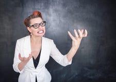 Gniewny nauczyciel w szkłach na blackboard tle zdjęcia stock