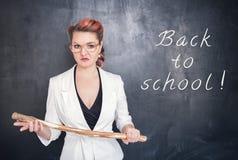 Gniewny nauczyciel z drewnianym kijem na chalkboard obraz stock