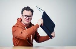 Gniewny programista rzuca laptop w kamerę z szkłami fotografia stock