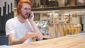 Gniewny rudzielec mężczyzna krzyczy, opowiadający na telefonie komórkowym w kawiarni zdjęcie wideo