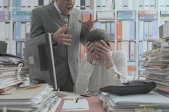 Gniewny szef wrzeszczy przy jego m?odym pracownikiem zdjęcie royalty free