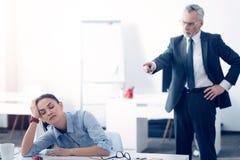 Gniewny szef wrzeszczy przy zmęczonym żeńskim urzędnikiem fotografia stock
