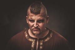 Gniewny Viking w wojownika tradycyjnych ubraniach, pozuje na ciemnym tle obrazy stock
