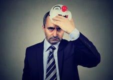 Gniewny w średnim wieku biznesowy mężczyzna bierze daleko szczęśliwą błazen maskę fotografia stock