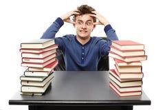 Gniewny zaakcentowany studencki obsiadanie przy jego biurkiem z rękami na hea obraz royalty free