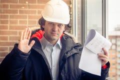 Gniewny zdegustowany budowniczego pracownik w hełmie z projektów rysunków planami w jego jeden telefonie komórkowym w inny i ręce obrazy royalty free