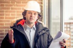 Gniewny zdegustowany budowniczego pracownik w hełmie z projektów rysunków planami w jego jeden telefonie komórkowym w inny i ręce zdjęcie stock