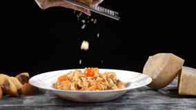 Gnisslande hårdost för kock Matlagningskaldjurpasta Ultrarapid av en kockrivjärnost, typisk italiensk ost, pasta på arkivfilmer