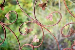 Gnisslande staket för rostig metall mot den suddiga gröna bakgrunden royaltyfri foto