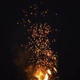 Gnistor från brasa i natten med mörk bakgrund royaltyfri foto