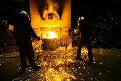 Gnistor från smältande stål, män som håller ögonen på moussera smältande stål i panna av gjuterit arkivfoto