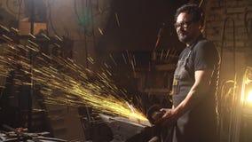 Gnistor under klipp av metallvinkelmolar Arbetare som använder den industriella molar Royaltyfri Foto