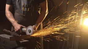 Gnistor under klipp av metallvinkelmolar Arbetare som använder den industriella molar Royaltyfria Bilder