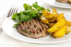 Gnälla hamburgaren med den grillade potatisen, sidosalladen och kryddorna på wh Arkivbilder