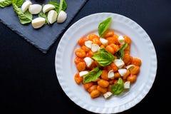 Gnocchi alla Sorrentina in der Tomatensauce mit grünen frischen Basilikum- und Mozzarellabällen diente auf einer Platte lizenzfreie stockfotos