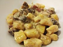Gnocchi avec les champignons de paris, la crème et le lard photo libre de droits
