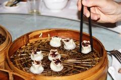 Gnocchi bolliti in un piatto di vimini sul tavolo da pranzo cinese Fotografia Stock