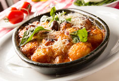 Gnocchi. Clay casserole Gnocchi hot plate wood fired with rich creamy sauce and fresh basil on a restaurant table. See more italian dishes royalty free stock photos