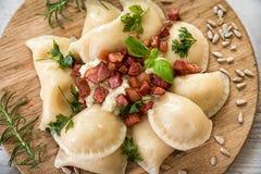 Gnocchi da batata enchido com queijo dos carneiros com bacon roasted na tabela de madeira fotos de stock