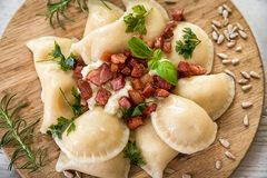 Gnocchi de la patata relleno con queso de las ovejas con tocino asado en la tabla de madera fotos de archivo