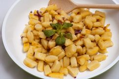 Gnocchi on the frying pan with wooden spoon. Stock Photos