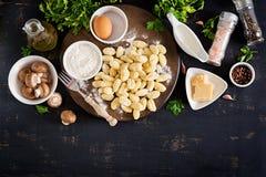 Gnocchi hecho en casa crudo con una salsa cremosa de la seta y Gnocchi hecho en casa parsleyUncooked con una salsa cremosa y un p imagenes de archivo