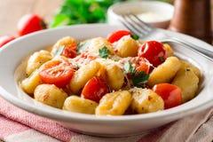 Gnocchi italien fait maison avec la tomate, l'ail, le persil et le parmesan sur la table en bois Photographie stock